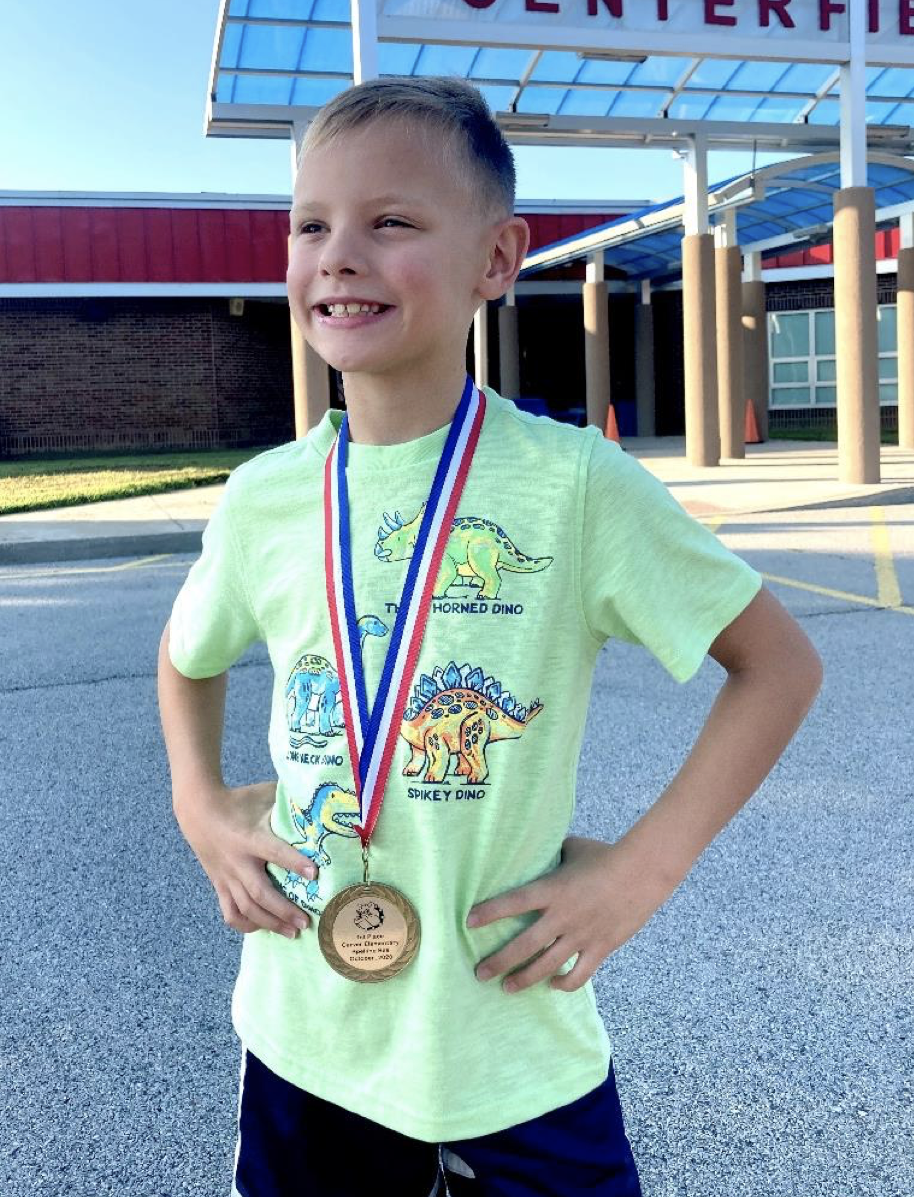 A picture of a kid proudly displaying an athletic and academic metal from presentation solutions recognizer machine