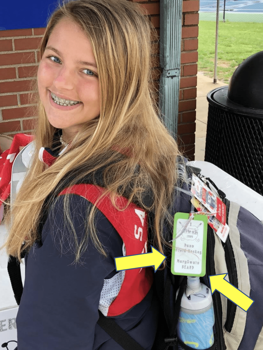 A student proudly showing off Her backpack and tags